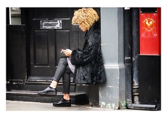 waiting on the doorstep (handheld-films) Tags: candid street portrait portraiture girl woman women london black red doorway doorstep door fur coat city metropolis people sitting seated selfabsorbed individual england anticipation