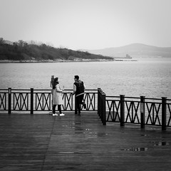 Sharing the time (Go-tea 郭天) Tags: qingdaoshi shandongsheng chine cn enjoy enjoying time moment couple boy girl young man woman together love relationship relation qingdao huangdao sea water puddle side deck wood wooden platform 2 day skewer coats rain share sharing harmony witness back backside canon eos 100d 50mm prime street urban city outside outdoor people bw bnw black white blackwhite blackandwhite monochrome naturallight natural light asia asian china chinese shandong