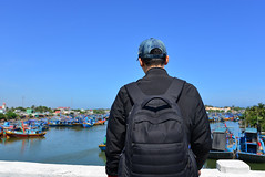 Asian man looking at the sea with fishing boats (phuong.sg@gmail.com) Tags: above adventure asian backpack backpacking bay beautiful beauty black clouds day daylight daypack destination explore exploring ferns hike hiker hiking horizontal landscape lifestyle look male man mountain natural nature ocean overlooking pacific scenic sea see space travel trip vacation vietnam view visiting vista water