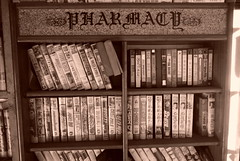 """Korea Daejeon retro VHS rental shop still surviving in 2017 - """"Do I Owe Any Late Fees?"""" (moreska) Tags: korea daejeon vhs video rental store tapes videocassettes 2017 oldschool disappearing faded blackandwhite sepia monochrome indoor creaky dusty fonts shelves pharmacy spines displays clamshells analogue t120 skc labels momandpop neighborhood nostalgia collectibles 대전 rok asia"""