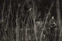 sosta (pamo67) Tags: pamo67 break pausa stop rest seduto sitting uomo man tralecanne amongthereeds bn blackwhite bw bianconero pasqualemozzillo panchina bench riva shore lago lake bici bike monochrome monocromo fili wires
