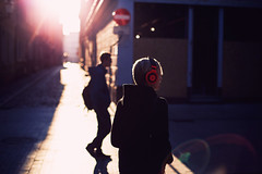 Sonic Boom (ewitsoe) Tags: headphones man woman walking oldmarket music flare canon eos 5ds 50mm fullframe sunrise dawn street city urban hipster musical erikwitsoe ewitsoe people listening head glare sunflare lensflare poznan poland polska