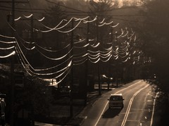Murrysville Late Afternoon (Sea Moon) Tags: wires reflections sunlight road cars street poles telephone telephoto sepia sunshine curves catenary
