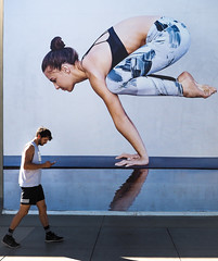 Head-to-Head (Feldore) Tags: ad yoga man street poster billboard candid wall walking past balancing santa monica california feldore mchugh em1 olympus 1240mm juxtaposition