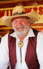 Yep, Still in Texas (wyojones) Tags: texas tomball tomballgermanheritagefestival costume attire hat beard man gentleman grayhair whitebeard festival cowboy bolotie cowboyhat vest smile sodas rootbeer sarsaparilla rattlesnakehatband cougar deerantler people texan hatband bigsmile