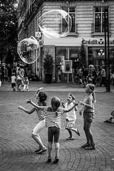 Bubble game. (Jérôme Cousin) Tags: street bw white black monochrome children soap nikon noir child bubbles nb bubble childrens enfants monochrom nikkor childs rue et enfant loire blanc bulles nantes 44 bulle savon atlantique 24120 d700