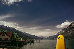 Yellowolf (Мaistora) Tags: lake water marina boats surfboard paddleboard yellow bright vivid vibrant contrast hills mountains alps steep high rocky snow winter spring sky clouds skyline valley sun sunshine sunlight sunny warm scape landscape lakescape skyscape nature relax recreation leisure holidays vacation travel tourism