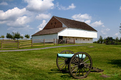 The Trostle Barn at Gettysburg (Rock Steady Images) Tags: camera blue trees vacation sky usa cloud brick green field grass bronze barn canon fence eos pennsylvania events wheels places equipment gettysburg cameras 7d processing damage handheld 200views battlefield 50views lenses cartrip topaz 25views niksoftware gettysburgnationalbattlefield bypaulchambers canonef2470mmf28iiusm lightroom4 photoshopcs6 rocksteadyimages trostlefarmblue