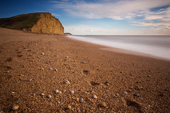 (Claire Hutton) Tags: uk longexposure blue winter england sky cliff sun motion color colour beach water yellow clouds contrast coast seaside movement alone harbour stones empty south smooth footprints sunny pebbles le dorset milky silky csc westbay eastcliff ndfilter jurassiccoast 10stop sonynex5r