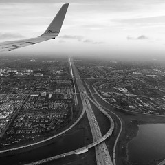 13 Jan 2014 (Rob Rocke) Tags: sky blackandwhite bw cars water monochrome clouds buildings flying blackwhite inflight wings miami aviation airplanes flight cities cityscapes highways roads sprawl americanairlines development birdseyeview aa ratrace windowseat instagram