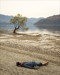 wanaka-6409-ps-w (pw-pix) Tags: beach sand mud gravel stones water man person lying resting relaxing shoes glasses pantsrolledup tree thattree famoustree cliche reflections shore sandy gravelly mountains haze hazy cloudy overcast clouds cloud lakewanaka wanaka southernalps skifields southisland nz newzealand