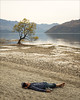 wanaka-6409-ps-w (pw-pix) Tags: beach sand mud gravel stones water man person lying resting relaxing shoes glasses pantsrolledup tree thattree famoustree cliche reflections shore sandy gravelly mountains haze hazy cloudy overcast clouds cloud lakewanaka wanaka southernalps skifields southisland nz newzealand peterwilliams pwpix wwwpwpixstudio pwpixstudio