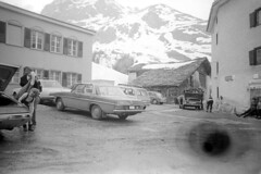 04a3471 32 (ndpa / s. lundeen, archivist) Tags: nick dewolf nickdewolf bw blackwhite photographbynickdewolf film monochrome blackandwhite april 1971 1970s 35mm europe centraleurope switzerland swiss alpine alps graubünden grisons easternswitzerland suisse schweitz mountains peaks snow snowy snowcovered landscape swissalps unidentified village building buildings parkinglot car cars vehicle vehicles automobile automobiles people skiarea