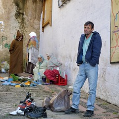 Shoes for sale (halifaxlight) Tags: street man vegetables square women shoes sitting market morocco medina talking soe traditionaldress sellers chefchaouene