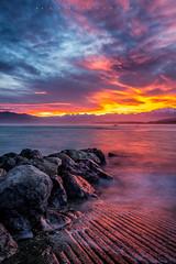 Sunset at Kaikoura (Fernandez Barrett) Tags: sunset newzealand beach nature water clouds canon landscape rocks textures nz southisland kaikoura vibrantcolours skycloudssun canoneos7d fabphotography fernandezbarrett