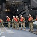 Sailors haul in a spring line to secure the Improved Navy Lighterage System Roll-on/Roll-off Discharge Facility.