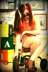 Novelty (Kelly McCarthy Photography) Tags: woman beautiful sunglasses fashion female vintage pose toys model dress legs bokeh tricycle retro redhead lolita pigtails catchycolorsorange orangedress heartshapedglasses bokehwhores vision:text=062
