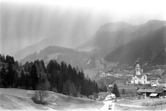 04a3571 16 (ndpa / s. lundeen, archivist) Tags: nick dewolf nickdewolf bw blackwhite photographbynickdewolf film monochrome blackandwhite april 1971 1970s 35mm europe centraleurope switzerland swiss alpine alps graubünden grisons easternswitzerland suisse schweitz mountains swissalps ontheroad roadtrip town village tiefencastel building church architecture steeple tower kirchststefan ststephenchurch ststefan kirche buildings hill hilltop landscape house houses home homes road highway street cars vehicles automobiles