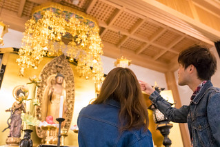 Young couple looking at Buddha statues in Hyakumanben Chionji temple, Kyoto