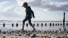 Broken Stones 44/156 (markfly1) Tags: west wittering sussex england countryside beach sea sand pebbles stones groins wooden posts sun sunny tip toe funny candid image 50mm nikon d750 family boy child kids children