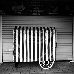 Coffee (Andrew Malbon) Tags: coffee tea stripes wheel shuttered shutters blinds closed shopwindow shops stall market fairground funfair clarencepier pier portsmouth southsea southseacommon southcoast solent leica leicam9 m9 rangefinder zeiss carlzeiss 21mm biogon2128zm biogont2821 biogon wideangle leendgrad lee06ndsoftgrad lee06nd lee handheld street streetphotography onstreet monochrome mono blackwhite black white