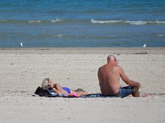 Couple in the April Sun (mikecogh) Tags: glenelg sunbathing couple bald reading shore