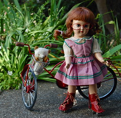 Toni and her Bike (Emily1957) Tags: toys toy dolls doll dewdropteddybears bismark toni hardplastic bike bicycle red braid braids pigtails plaits plait ricrack 1950s teddybear rollerskates sidewalk light naturallight nikond40 nikon kitlens