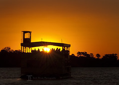 Sunset on the Zambezi (Beth Wode) Tags: africa sunset people orange black silhouette yellow river landscape boat nikon sundown beth zimbabwe sunburst sunrays zambia zambezi rivercruise zambeziriver wode d7000 bethwode