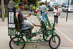 Taxi for Tips (bill.d) Tags: woman man bicycle person us waiting downtown sitting michigan taxi unitedstatesofamerica streetphotography kalamazoo horn canonef28135mmf3556is quadracycle eos60d kiaartfair