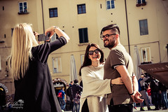 Having fun in the Piazza dell Anfiteatro, Lucca (by Amy Davies, Plymouth, MA) Tags: 2017 fujifilmxt2 italy lucca march walkingaround happypeople takingphotos piazza italia tuscany toscana anfiteatro piazzadellanfiteatro laughing joy playingwithphones youngpeople beautifulpeople italians joyful