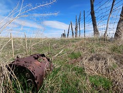 1 with Holes or Holy Bucket (Robert Cowlishaw-Mertonian) Tags: stagnation decay mertonian bucket uselessbucket robertcowlishaw wilderness canon powershot g7x mark ii canonpowershotg7xmarkii sky clouds grass blue green fence wire lookingup empty holy nature safe