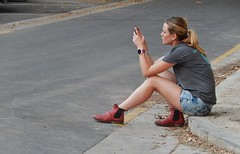 Communicating from the Gutter (mikecogh) Tags: woman boots communication ponytail gutter texting 2014 womadelaide