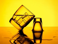 Tipsy (Karen_Chappell) Tags: tilt balance glass orange yellow ice water icecubes shotglass glasses stilllife reflection liquid alcohol beverage product reflections