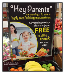 Three Suggestions: The Parent in the Photo Should Zip Up Her Jeans; the Jackass in the Grocery Store Who Smeared Something on the Face of the Girl in the Photo Should Be Forced to Eat Rotten Eggs; and Hungry Children Should Be Fed (Doyle Wesley Walls) Tags: lagniappe 4490 iphonephoto healthysnacks parent child mom daughter food free grocerystore fruit zipper photograph doylewesleywalls