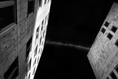 Wall to Wall Thinking (claustral) Tags: windows sky bw monochrome buildings skåne contrail highcontrast walls malmö