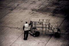 LHR lonesome worker : Observational Photography - Course task 29 (Coisroux) Tags: aviation engineering obeservational heathrow blackandwhite monochrome starkness industry airports airside concrete geometrical stains steel steps workmen d5500 nikond dirt squares linear lines equipment aircraft machinery