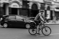 London   |   Bicycle vs Hybrid Car (JB_1984) Tags: bicycle cycling cycle bike toyota prius hybridcar cyclist movement motion blur pan streetphotography street blackandwhite bw mono piccadillycircus cityofwestminster london england uk unitedkingdom