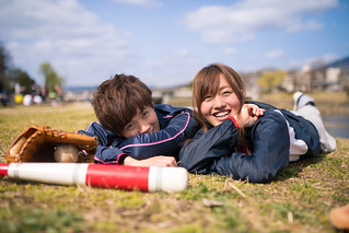 Happy young athlete couple lying on grass together after playing baseball