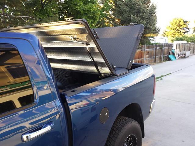 aluminum s dodge hd ram diamondback bluetruck diamondplate tonneaucover truckbedcover dr09 twopanelsopen driversideheadlightview blacklinex ruggedblack heavydutytruckbedcover