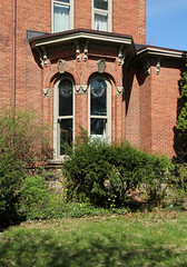 House — Coldwater, Michigan (Pythaglio) Tags: house dwelling residence historic italianate ornate brick twostory coldwater michigan branch county 11 windows roundarched hoodmolds keystones carved carvings leaves dripstones polygonal bay bush foliage grass sky blue