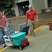 Chancellor Randy Woodson (r) rolls a suitcase up to Lee Residence Hall for a family moving their student onto campus for the Fall.