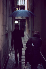 A rainy day in Venice... (Melinda Szente) Tags: street city venice people italy woman rain umbrella canon photography 50mm photo flickr afternoon shadows gloomy cloudy dusk streetphotography atmosphere naturallight streetscene rainy romantic softfocus youngman narrowstreet canoneos450d arainydayinvenice vision:outdoor=0784 melindaszentephotography