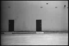 I'll take what's behind door number 2, Bob. (FreezerOfPhotons) Tags: leicam5 nokton40mm14sc cosinavoigtlandernokton40mmf14sc singlecoatedlens fujineopan400 legacypro xtol concreteblock metal door paint concrete pavement