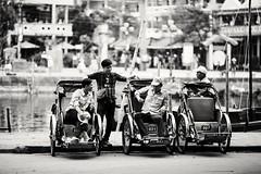 Vietnamese Streetlife (desomnis) Tags: street streetphotography urban monochrome bw blackandwhite monochrom vietnam asia southeastasia hoi an hoian people rickshaw rickshaws men canon6d 135mm canon135mmf20 streetlife