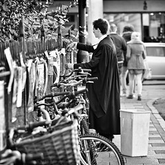 """We cuts the nasty posters and we puts them in the bin."" (PhotoJunket) Tags: cambridge signs dof bokeh candid streetphotography bikes bicycles posters cutting gown removal marketsquare removing finery polishedshoes deressed vision:outdoor=0931"