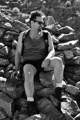 Instant Mohawk in the Wind (Blue Rave) Tags: bw blackandwhite 2017 bloke dude guy male mate people meninshorts guysinshorts tanktop goatee nature hike hiking sunglasses rayban wayfarer backpack legs thighs handsome sexy stud hair menshair cairn sitting rugged