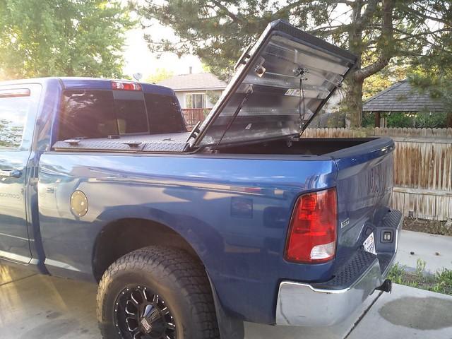 aluminum s dodge hd ram diamondback bluetruck diamondplate tonneaucover truckbedcover dr09 driversideview onepanelopen blacklinex ruggedblack heavydutytruckbedcover