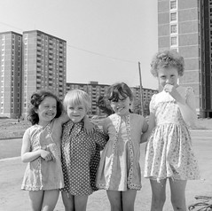 There's always one!  Four little girls in the shadow of the Ballymun tower blocks. (National Library of Ireland on The Commons) Tags: elinorwiltshire rolleiflexcamera rolleiflex wiltshirephotographiccollection nationallibraryofireland elinoro'brienwiltshire reginaldwiltshire ballymun towerblocks fourgirls sunshine dresses theseventowers 1969 kids flats