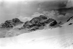 04a3371 28 (ndpa / s. lundeen, archivist) Tags: nick dewolf nickdewolf bw blackwhite photographbynickdewolf film monochrome blackandwhite april 1971 1970s 35mm europe centraleurope switzerland swiss alpine alps graubünden grisons stmoritz easternswitzerland suisse schweitz mountains peaks snow snowy snowcovered skiresort skiarea skislopes skiing landscape people skiers slopes swissalps