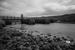 Three Quarter Bridge B/W (Willhill2910) Tags: threequarterbridge nikon nikond3200 amateur blackandwhite beach coast causeway causewaycoast coastline clouds discoverni discoverireland dark daylight exposure longexposure landscape pebbles scenic stone rocks rugged bridge portballintrae northernireland ireland sigma1020mm dunes